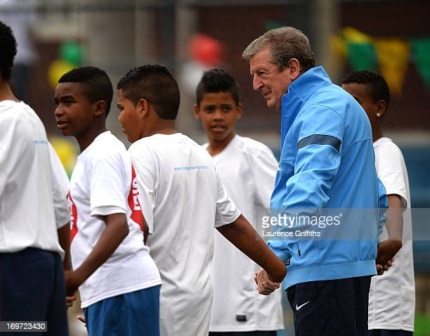 Manager Roy Hodgson of England joins in a training session with local children during a visit to a Sport Relief project on May 31 2013 in Rio de...