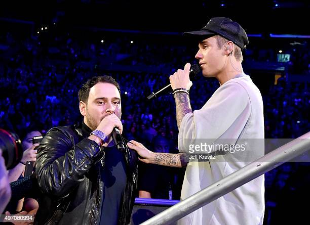 Manager Scooter Braun and singer/songwriter Justin Bieber hug onstage during an evening with Justin Bieber to celebrate the release of his new album...