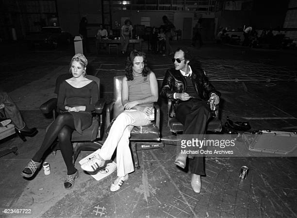 Manager Shep Gordon and musician Alice Cooper chat on a soundstage with a woman in circa 1975 in Los Angeles California