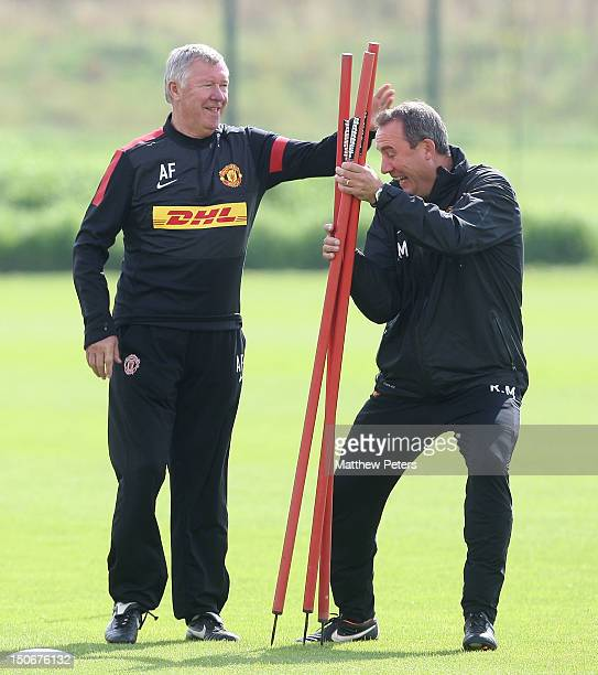 Manager Sir Alex Ferguson of Manchester United playfully hits First Team Coach Rene Meulensteen at Carrington Training Ground on August 24 2012 in...