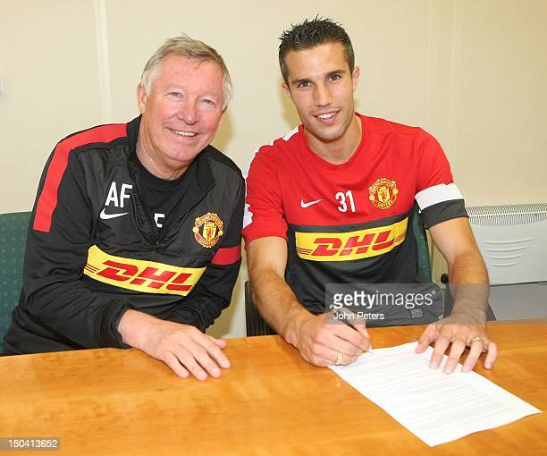 Manager Sir Alex Ferguson poses with Robin van Persie as he signs for Manchester United FC at their Carrington Training Ground on August 17 2012 in...