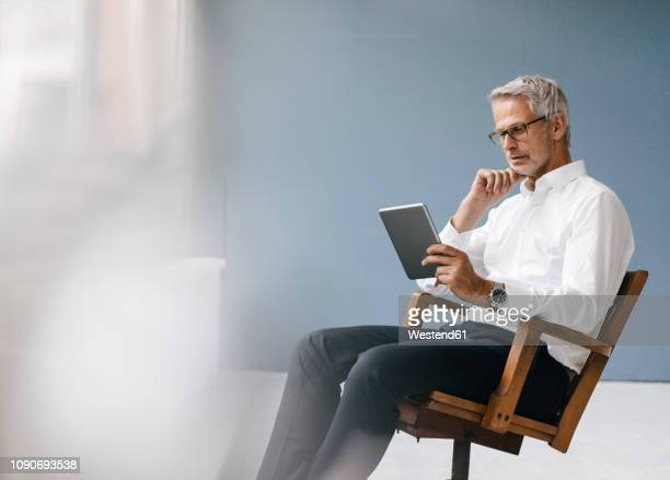 manager sitting in office, using digital tablet - information equipment stock pictures, royalty-free photos & images