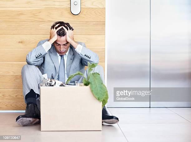 Manager seduto con la testa tra le mani fuori un ascensore