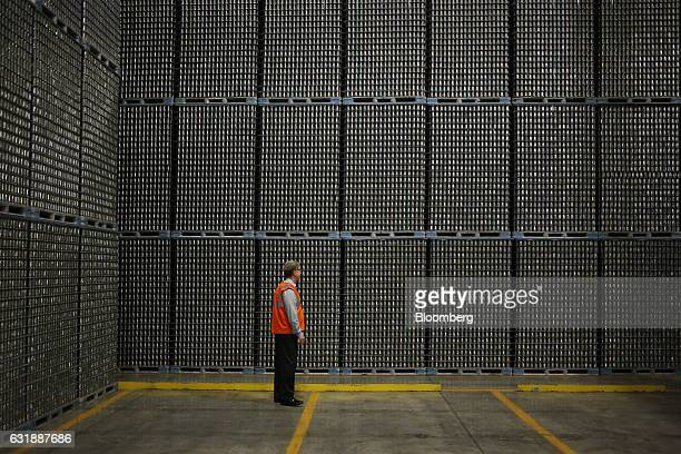 A manager stands next to pallets of aluminum food cans inside the warehouse at the Ball Corp beverage can manufacturing facility in Findlay Ohio US...