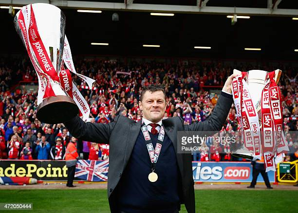 Manager Steve Cotterill of Bristol City celebrates with the League One Trophy and the Football League Trophy during the Sky Bet League One match...