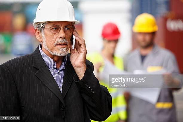 Gerente hablando hablando por teléfono al muelle comercial