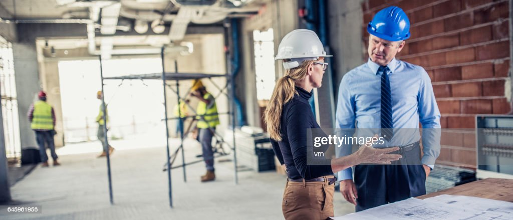 Manager talking to architect op bouwplaats : Stockfoto