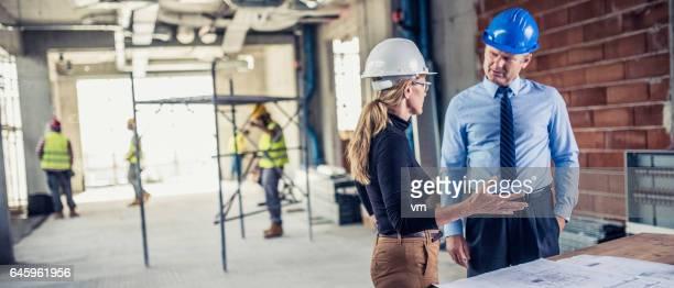 manager talking to architect op bouwplaats - incidental people stockfoto's en -beelden