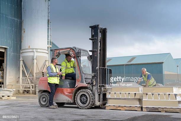 Manager talking to forklift truck driver outside architectural stone factory