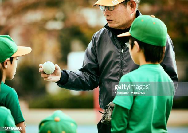 manager telling boy about pitching in baseball game - 絆 ストックフォトと画像