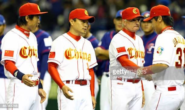Manager Terry Collins of Team China welcomes in the players for the national anthem during Game 3 of the 2009 World Baseball Classic Pool A match...