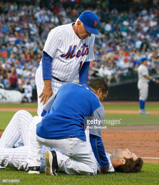 Manager Terry Collins of the New York Mets and trainer Ray Ramirez help Neil Walker of the New York Mets after he injuries himself running up the...