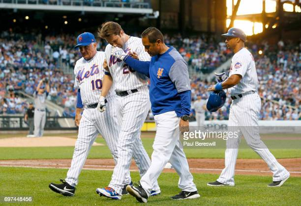 Manager Terry Collins of the New York Mets and trainer Ray Ramirez help Neil Walker of the New York Mets off the field after he injuries himself...