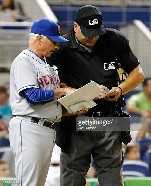 Manager Terry Collins of the New York Mets makes a lineup change with home plate umpire Jeff Nelson as his team played the Miami Marlins at Marlins...