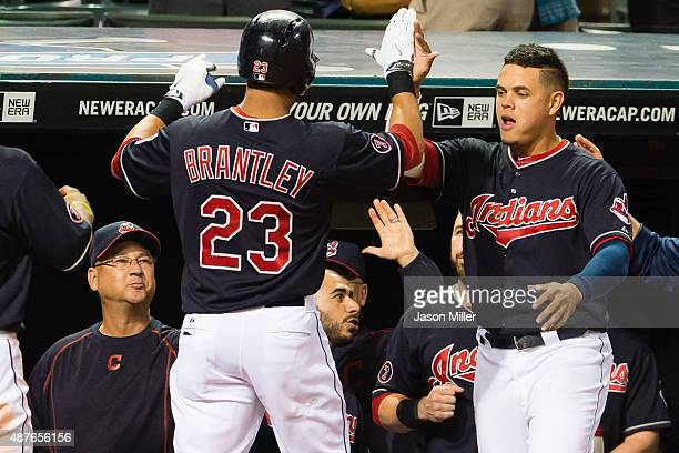 Manager Terry Francona and Giovanny Urshela celebrate with Michael Brantley of the Cleveland Indians after Brantley hit a two run home run during the...