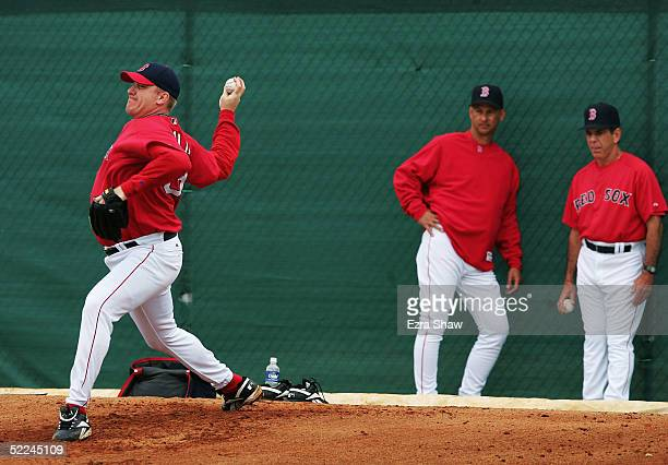 Manager Terry Francona and pitching coach Dave Wallace watch Curt Schilling of the Boston Red Sox pitch off the mound during practice at the Red Sox...