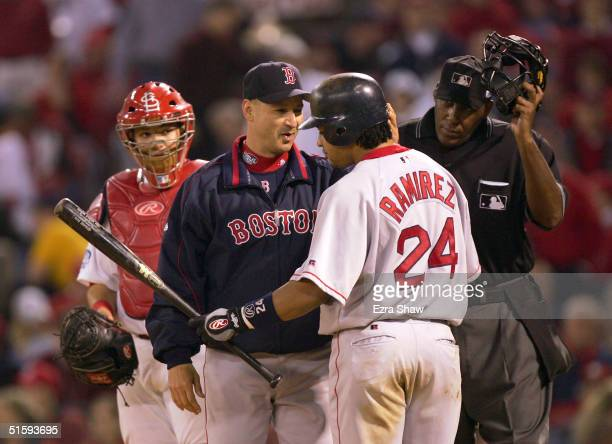 Manager Terry Francona of the Boston Red Sox and umpire Chuck Meriwether stand between catcher Yadier Molina of the St Louis Cardinals and batter...