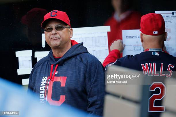 Manager Terry Francona of the Cleveland Indians looks out from the dugout while Bench Coach Brad Mills posts lineups on the wall before the start of...