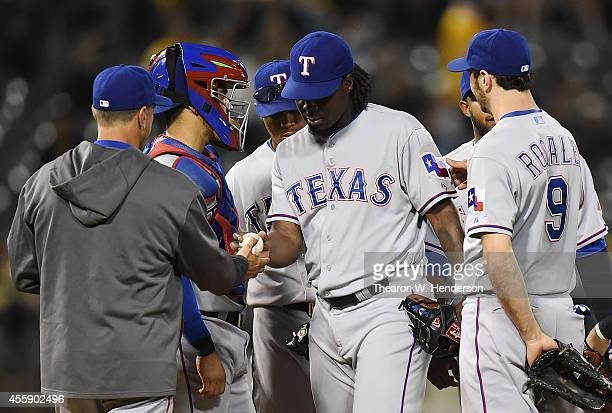 Manager Tim Bogar of the Texas Rangers takes the ball from pitcher Roman Mendez taken him out of the game against the Oakland Athletics in the bottom...