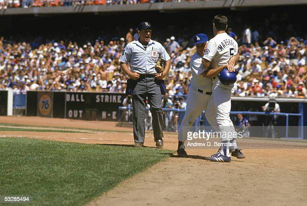 Manager Tommy Lasorda of the Los Angeles Dodgers restrains Mike Marshall during an argument with an umpire during a game in the 1987 season at Dodger...