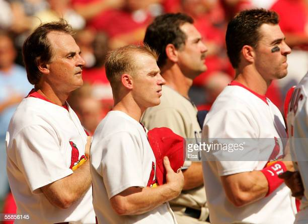 Manager Tony La Russa of the St Louis Cardinals stands with his team during singing of the National Anthem prior to the start of game one of the...