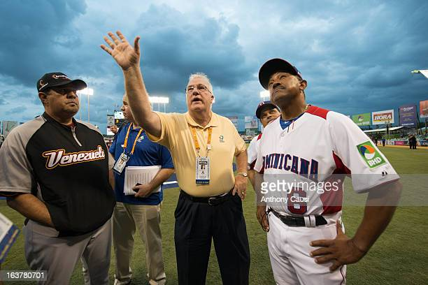 Manager Tony Pena of Team Dominican Republic and manager Luis Sojo of Team Venezuela are given the ground rules by MLB representative Larry Young...