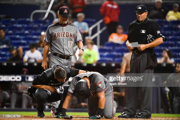 Manager Torey Lovullo and head trainer Ken Crenshaw tend to David Peralta of the Arizona Diamondbacks after being hit by a pitch in the ninth inning...