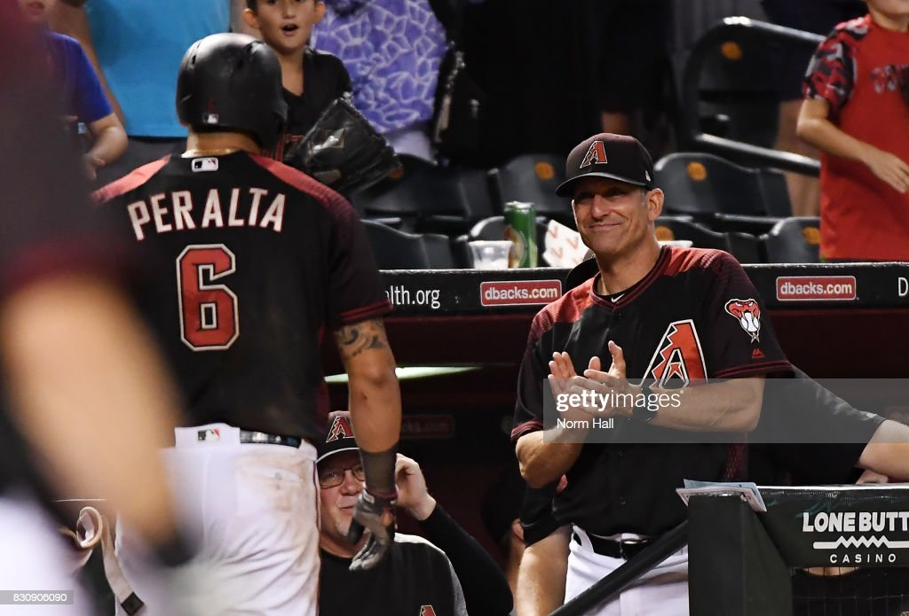 Manager Torey Lovullo #17 of the Arizona Diamondbacks congratulates David Peralta #6 for hitting an inside the park home run during the eighth inning against the Chicago Cubs at Chase Field on August 12, 2017 in Phoenix, Arizona. Diamondbacks won 6-2.