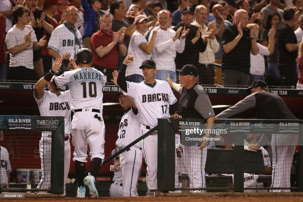 Manager Torey Lovullo #17 of the Arizona Diamondbacks high fives Deven Marrero #10 after scoring against the Los Angeles Dodgers during the seventh inning of the MLB game at Chase Field on May 1, 2018 in Phoenix, Arizona.