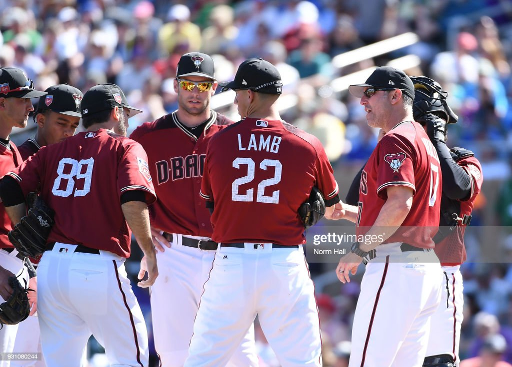 Manager Torey Lovullo #17 of the Arizona Diamondbacks talks with new pitcher Tyler Pill #89 as teammates Paul Goldschmidt #44 and Jake Lamb #22 listen in during the fourth inning of a spring training game against the Colorado Rockies at Salt River Fields at Talking Stick on March 12, 2018 in Scottsdale, Arizona.