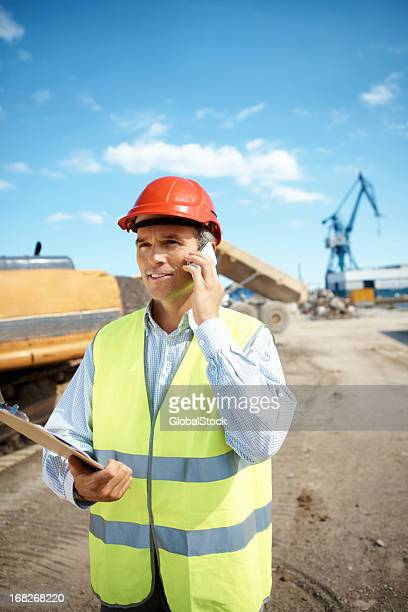 Manager using cellphone at construction site