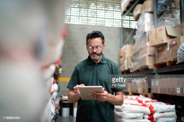 manager using his tablet working in warehouse / industry - control stock pictures, royalty-free photos & images