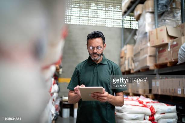 manager mit seinem tablet arbeitet im lager / industrie - business finance and industry stock-fotos und bilder