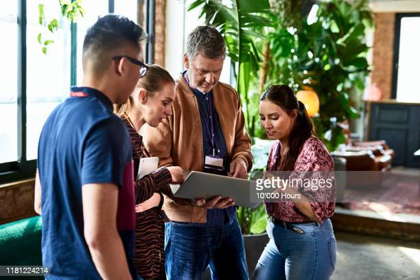 manager using laptop with team in office breakout area - manager stock pictures, royalty-free photos & images