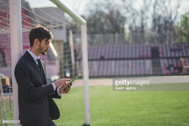 Manager using tablet on football field