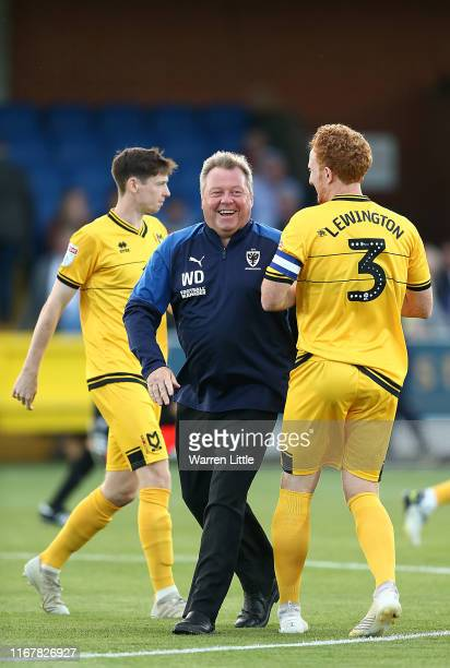 Manager Wally Downes of AFC Wimbledon shares a laugh with Dean Lewington Captain of MK Dons ahead of kick off in the Carabao Cup First Round match...