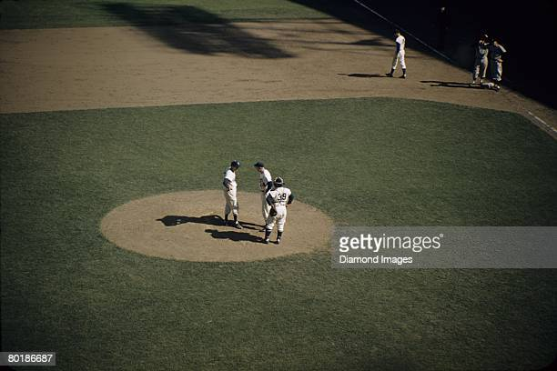 Manager Walter Alston visits pitcher Sal Maglie and catcher Roy Campanella of the Brooklyn Dodgers on the mound during game three of the World Series...