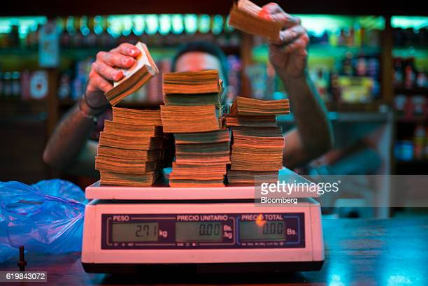 A manager weighs banknotes on a scale at a bakery in Caracas Venezuela on Thursday Oct 13 2016 Once one of the world's strongest currencies the...