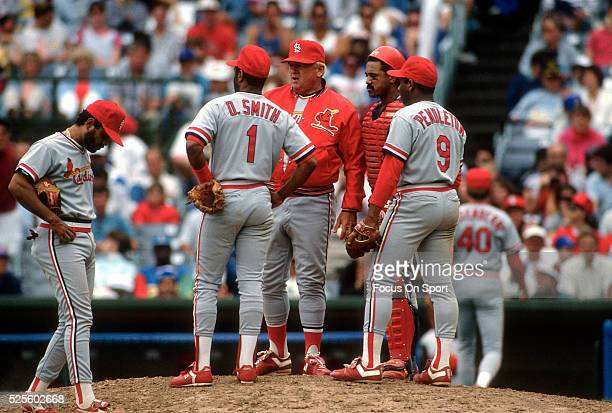 Manager Whitey Herzog of the St Louis Cardinals making a pitching change stands on the mound with payers Ozzie Smith Terry Pendleton and catcher Tony...