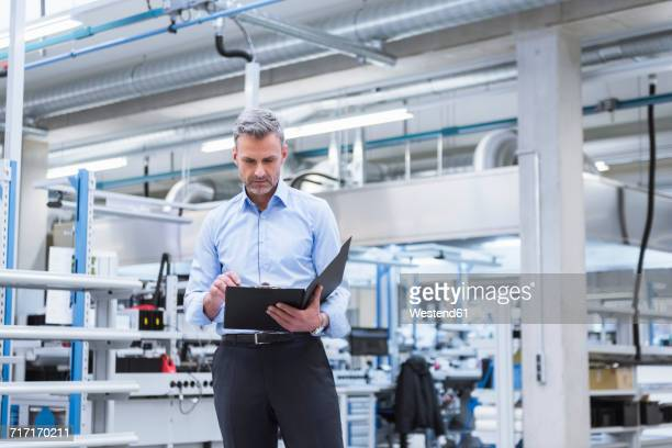 Manager with files walking through factory