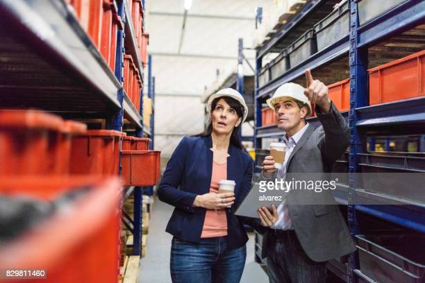 Manager with foremen controlling stock in warehouse
