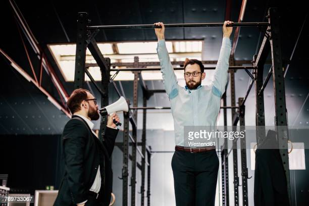 Manager with megaphone giving businessman hanging on bar orders