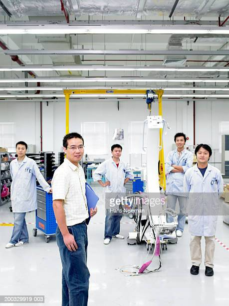 Manager with team in medical manufacture plant, portrait