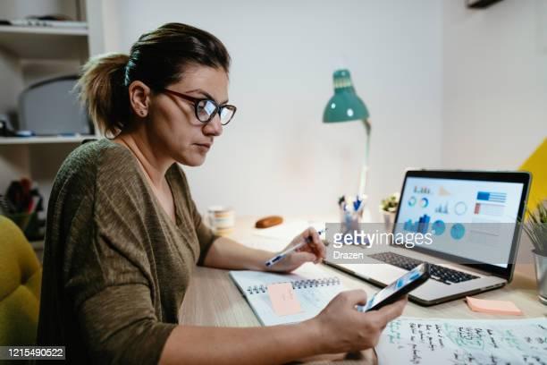 manager arbeitet von zu hause aus und koordiniert sich mit den mitarbeitern über die mobile app - börsenhandel finanzberuf stock-fotos und bilder