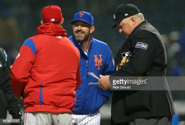 Managers Gabe Kapler of the Philadelphia Phillies and Mickey Callaway of the New York Mets meet as they exchange lineup cards as home plate umpire...
