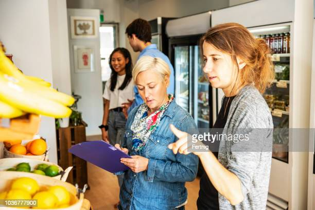 a managers of a small urban grocery store checking inventory - convenience store stock photos and pictures