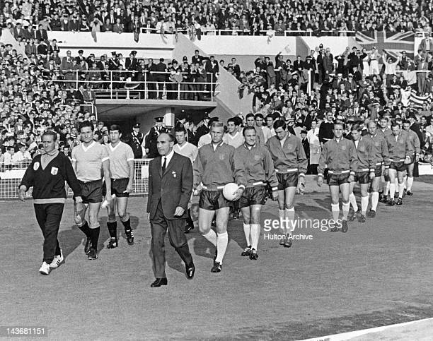 Managers Ondino Viera of Uraguay and Alf Ramsey of England lead their teams out for their first round Group 1 match in the World Cup at Wembley 11th...