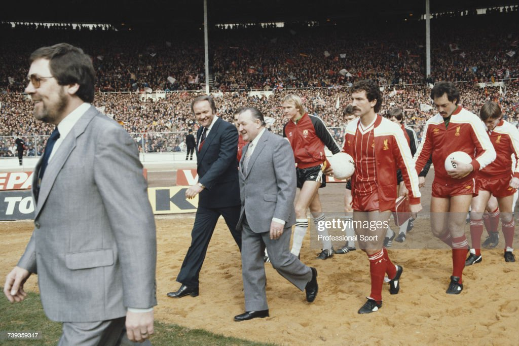 Managers Ron Atkinson (left) and Bob Paisley (1919-1996) lead players from their respective teams, Manchester United and Liverpool out on to the pitch prior to the start of the 1983 Football League Cup Final at Wembley Stadium in London on 26th March 1983. Liverpool would go on to beat Manchester United 2-1 to win the cup. Players pictured include Gary Bailey of Manchester United (4th from left) and Graeme Souness, Bruce Grobbelaar and Kenny Dalglish of Liverpool.