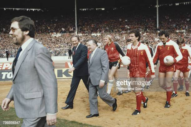 Managers Ron Atkinson and Bob Paisley lead players from their respective teams Manchester United and Liverpool out on to the pitch prior to the start...
