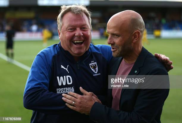 Managers Wally Downes of AFC Wimbledon and Paul Tisdale of MK Dons share a laugh ahead of kick off in the Carabao Cup First Round match between AFC...